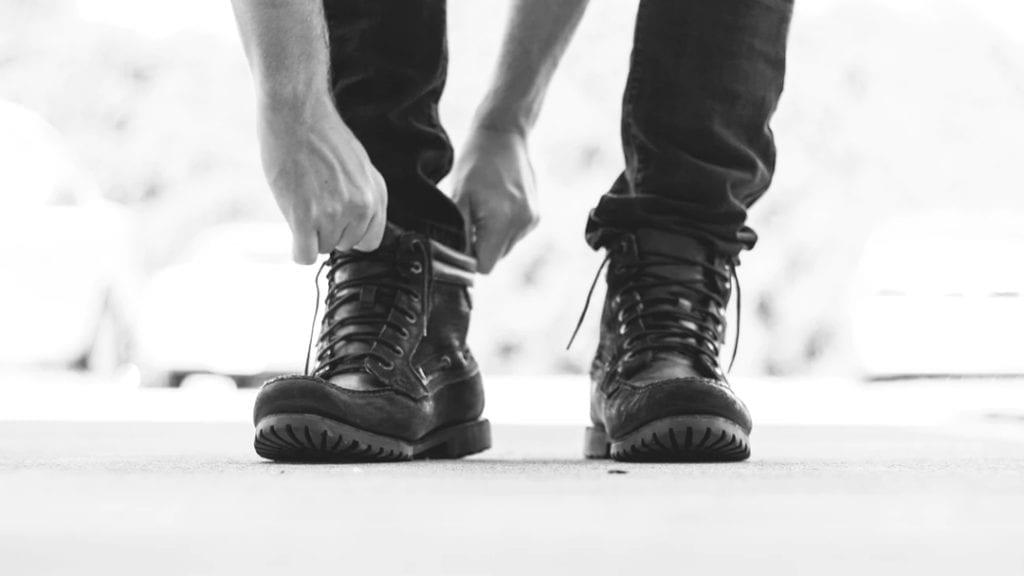 Man pulling on black Boots